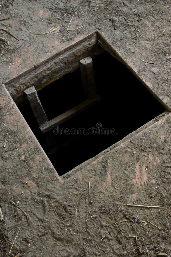 Hål i golvet av det gamla huset som leder för att förvara i källare arkivfoton