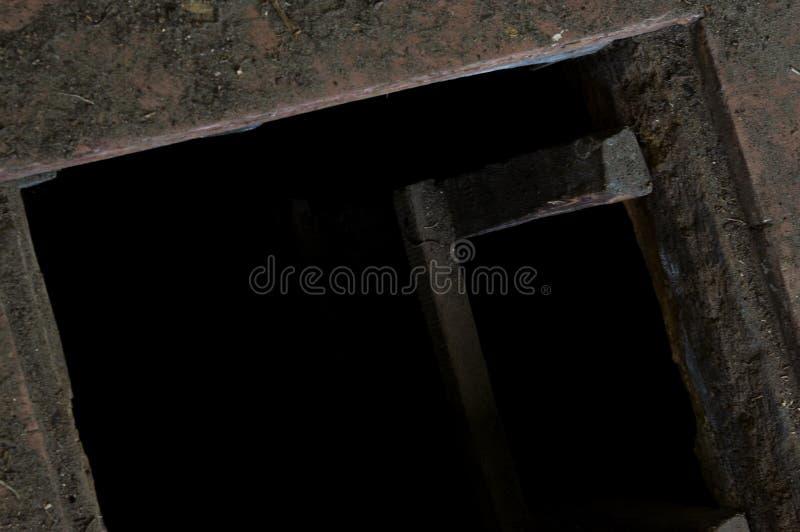 Hål i golvet av det gamla huset som leder för att förvara i källare royaltyfri bild