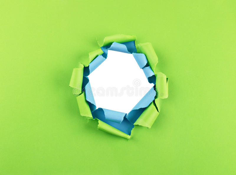 Hål i grönt och blått papper royaltyfri foto