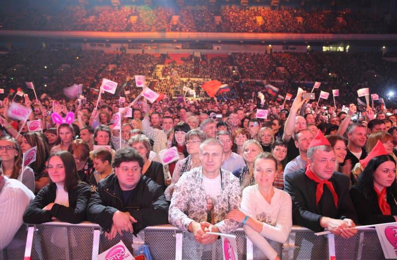 Hål med lyckliga ventilatorer, flaggor på konsert royaltyfri bild
