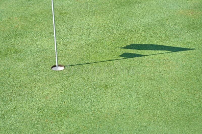 Hål och skugga av golfflaggan arkivbild