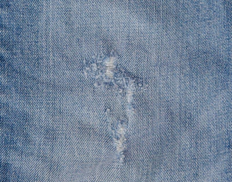 Hål och trådar på grov bomullstvilljeans Riven sönder förstörd sönderriven jeansbakgrund Övre blå jeantextur för slut arkivbilder