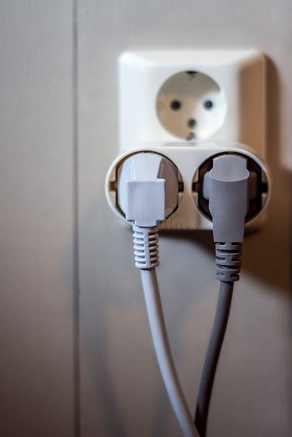 Håligheten på väggen med två pluged elektriska uttag och powercords arkivfoton