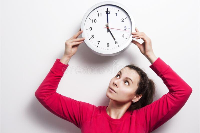 Håll ögonen på tidbegreppet Flickan rymmer den runda klassiska klockan över hennes huvud Den unga brunettkvinnan ser klockan arkivfoton