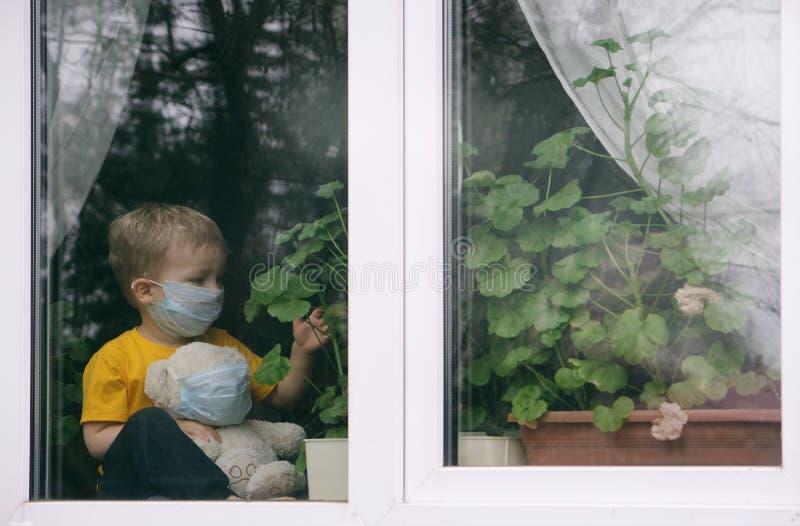 Håll dig i karantän i hemmet för att förebygga pandemier av coronavirus Ett barn med barnbjörn i skyddsmasker sitter på royaltyfri fotografi