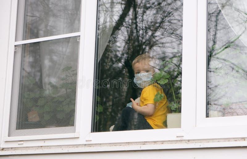 Håll dig i karantän i hemmet för att förebygga pandemier av coronavirus Sjuka barn med teddybjörn i skyddsmasker på fönsterbänk royaltyfria bilder