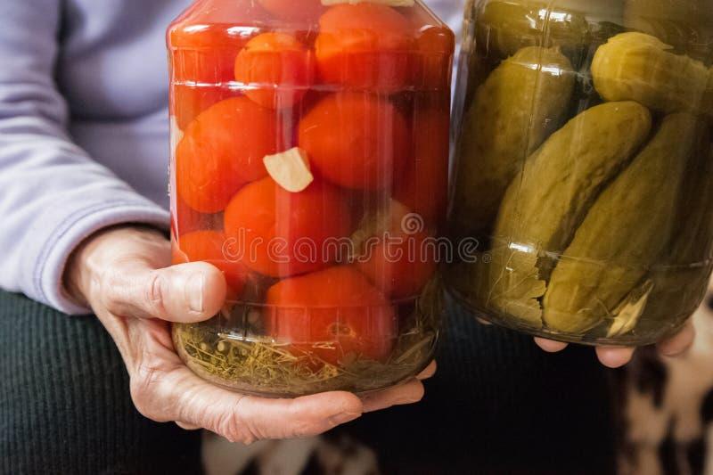 Håll för en gammal dam i hennes rynkiga händer en krus av gurkor och tomater Vinterförberedelser i banker royaltyfri bild