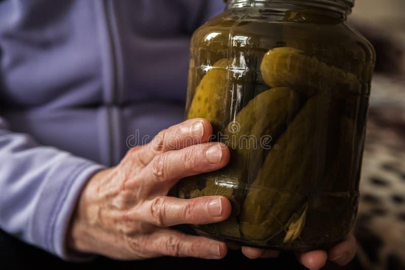Håll för en gammal dam i hennes rynkiga händer en krus av gurkor och tomater Vinterförberedelser i banker arkivbild
