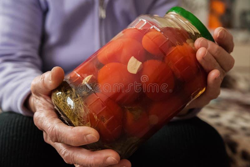 Håll för en gammal dam i hennes rynkiga händer en krus av gurkor och tomater Vinterförberedelser i banker royaltyfri foto