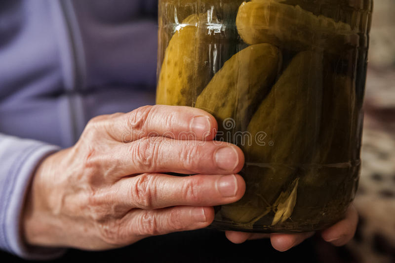 Håll för en gammal dam i hennes rynkiga händer en krus av gurkor och tomater Vinterförberedelser i banker arkivfoton