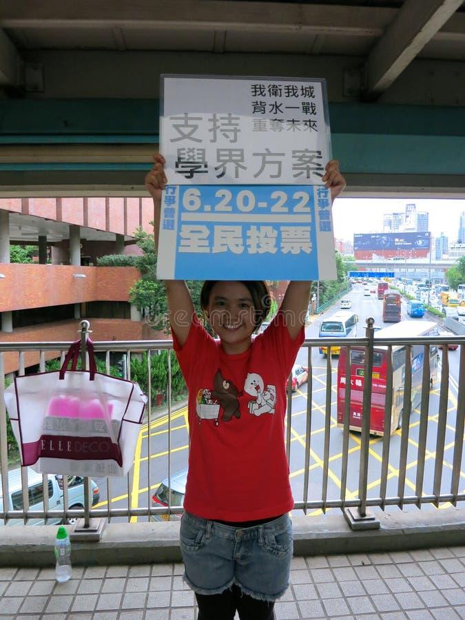 Håll för Scholarism demokratiperson som protesterar upptar det centrala tecknet royaltyfri foto