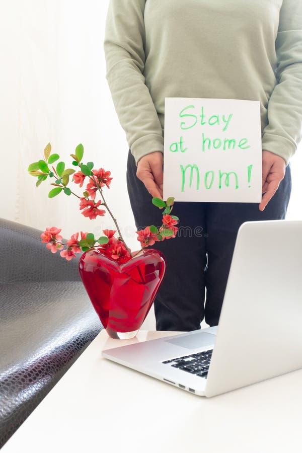 Håll kvar den bärbara datorn från mamma och mamma, vårblommor, rosa hand-sida blankt koronavirus-skärm 19 royaltyfri fotografi