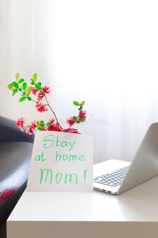 Håll kvar den bärbara datorn från mamma, vårblommor, rosa sida med blankt koronavirus 19 fotografering för bildbyråer