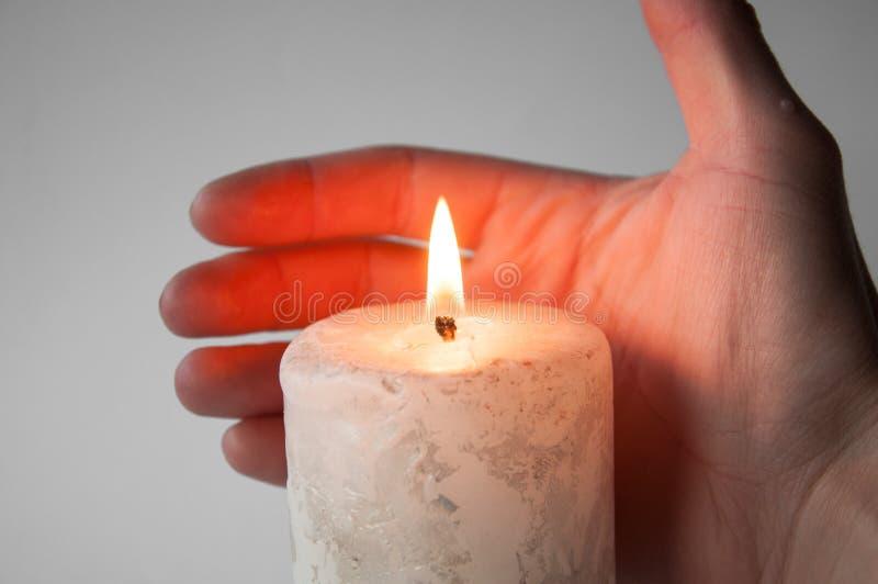 Håll räcker nära en brinnande vit stearinljus arkivbild