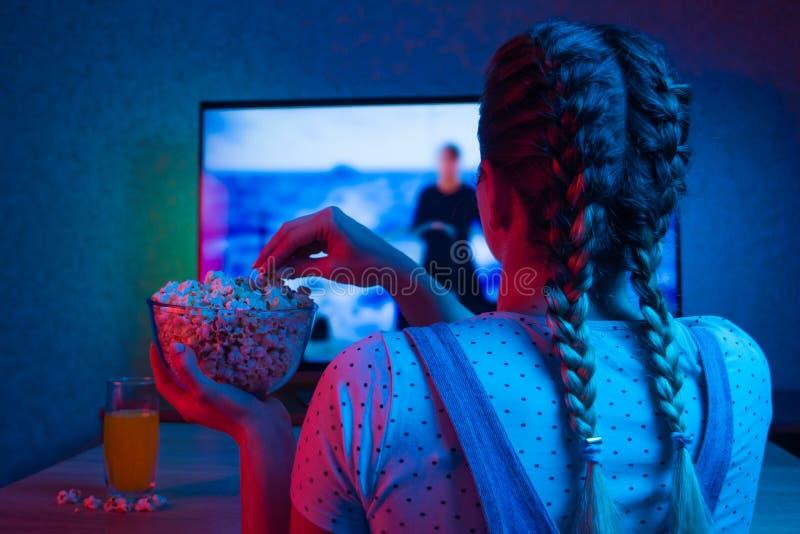 Hålla ögonen på en film med popcorn, färgrik kulör bakgrund Filmer filmer arkivfoto