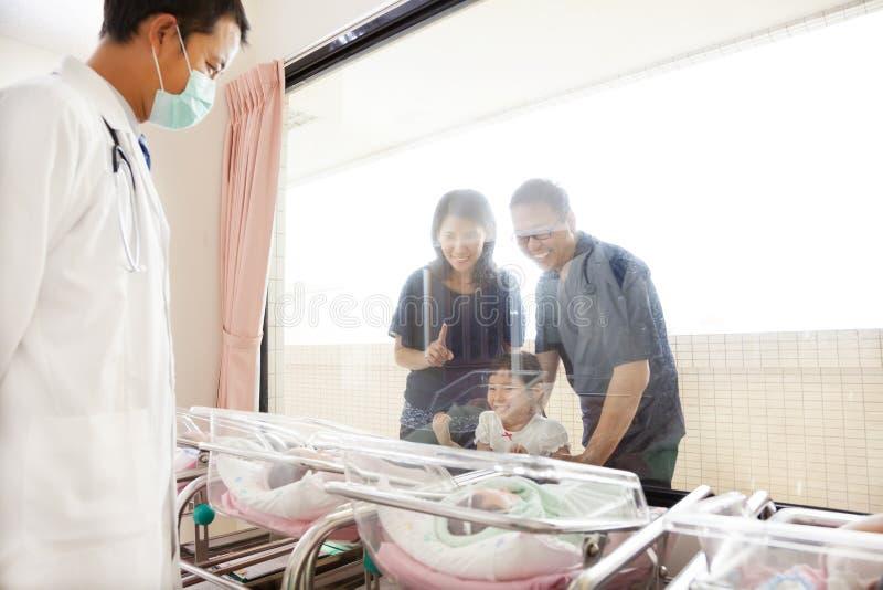 Hålla ögonen på för familj som är nyfött i barnafödandemitt och doktor royaltyfri foto