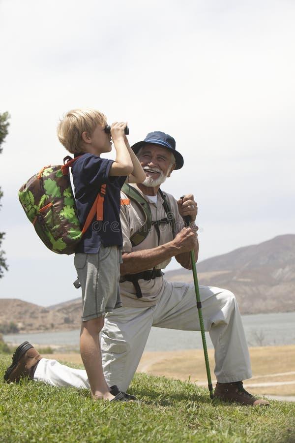 Hålla ögonen på för farfar- och sonsonfågel royaltyfri bild
