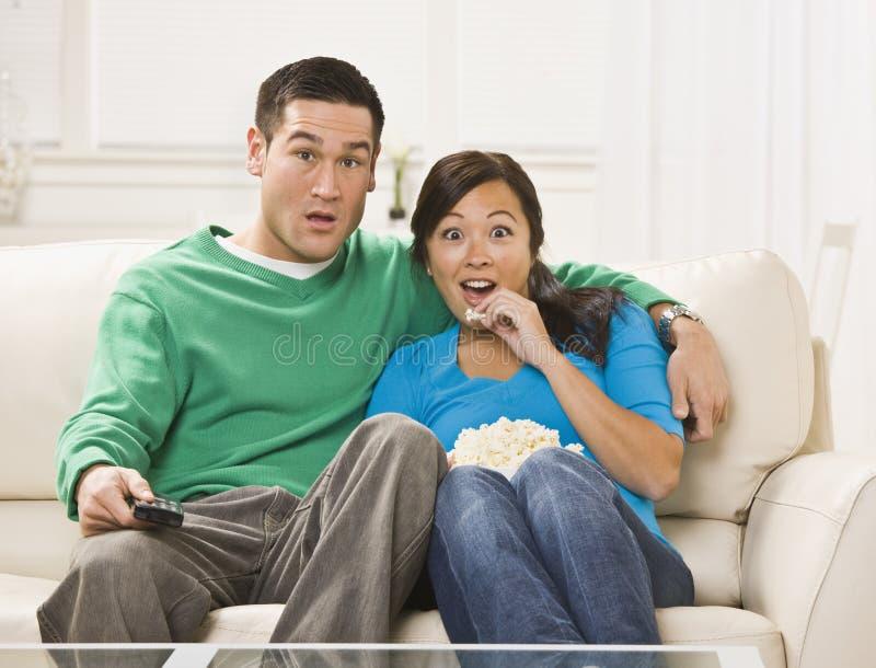 hålla ögonen på för tv för par förvånadt royaltyfria foton