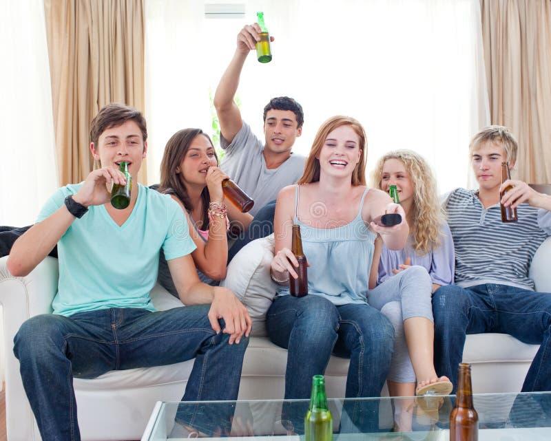 hålla ögonen på för tv för vänner för öl dricka home arkivbilder