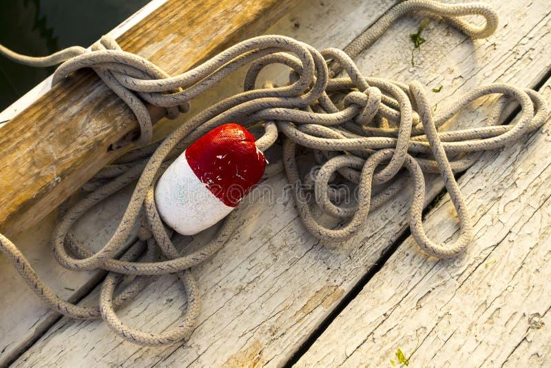 Hålla flytande röd vit på ett solbränt brunt rep som ligger på en skogsbevuxen fiska pir royaltyfri fotografi