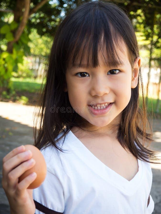 Hållande ägg för gullig asiatisk flicka i hand Ägg och le för visning Co arkivbilder