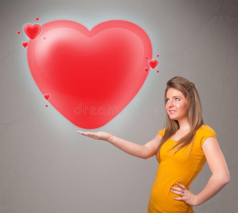 Hållande älskvärd röd hjärta 3d för ung lady arkivfoton