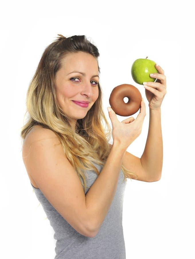 Hållande äpple för attraktiv kvinna och chokladmunk i sund söt skräpmatfrestelse för frukt kontra fotografering för bildbyråer