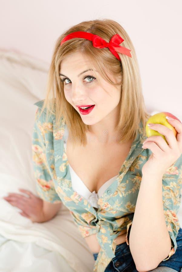 Hållande äpple för härlig blond för ung kvinna för blåa ögon sexig flicka för utvikningsbrud & se kamerasammanträde i vit säng royaltyfri bild
