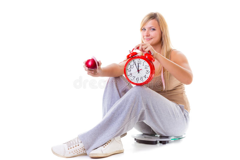 Hållande äpple för kvinna och att mäta bandet och klockan arkivfoto