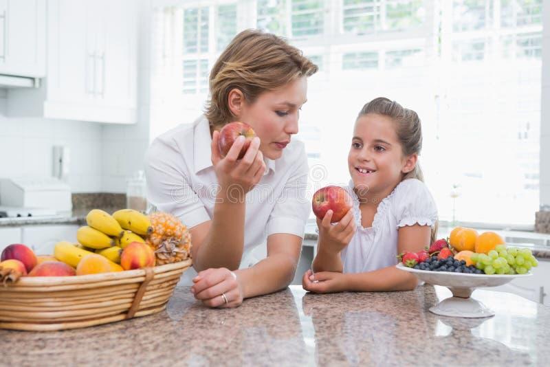 Hållande äpplen för moder och för dotter royaltyfria foton