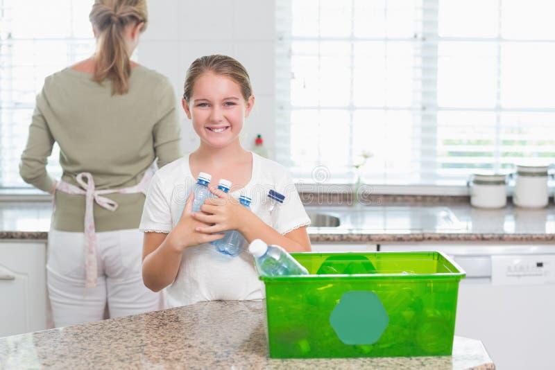 Hållande återvinningflaskor för lycklig liten flicka royaltyfria bilder