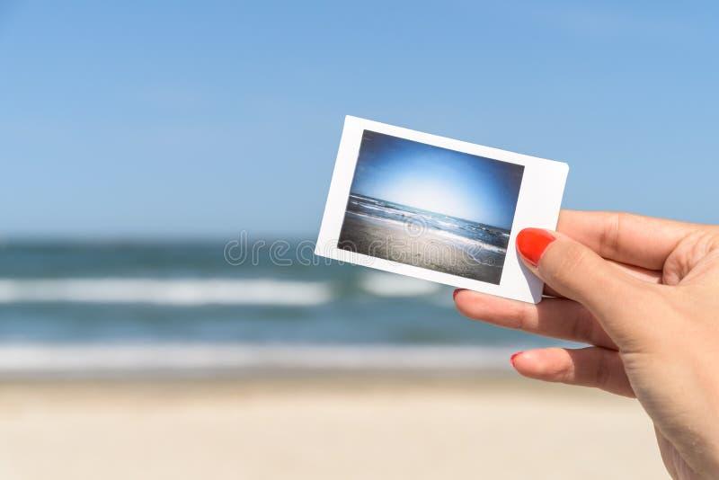 Hållande ögonblickligt foto för flicka av havsstranden arkivbilder