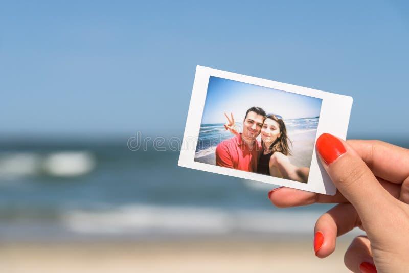 Hållande ögonblickligt foto för flicka av lyckliga par arkivfoto