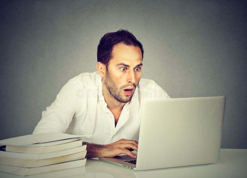 Hållande ögonen på bärbar dator för chockad man, medan studera arkivfoton