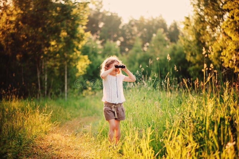 Hållande ögonen på fåglar för lyckligt barn med binokulärt i sommarskog fotografering för bildbyråer