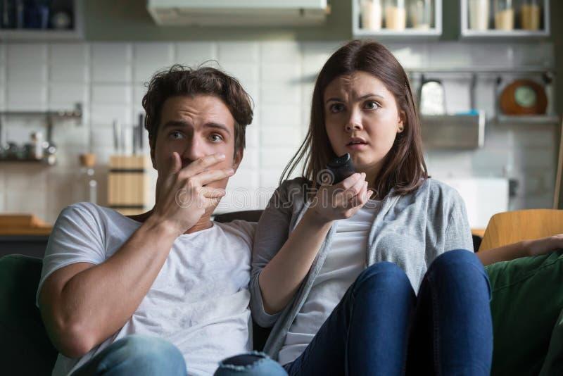 Hållande ögonen på fasafilm för förskräckta millennial par på tv hemma royaltyfria foton