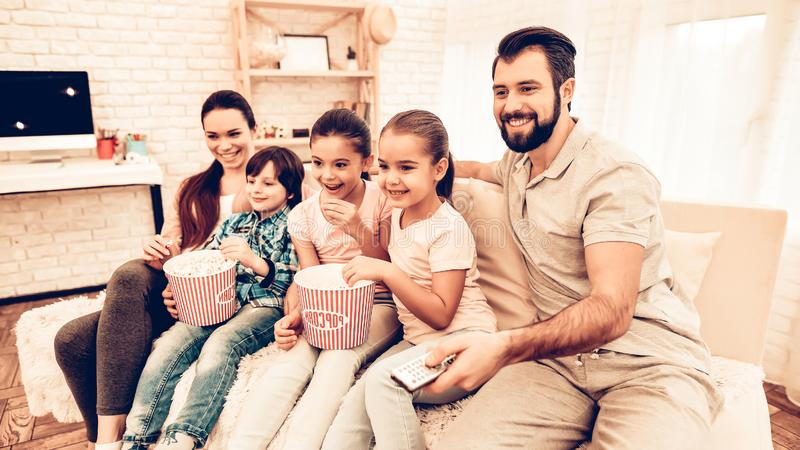 Hållande ögonen på film för älskvärd gladlynt familj hemma arkivbild