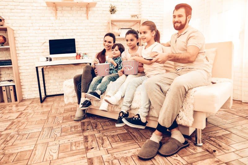 Hållande ögonen på film för älskvärd gladlynt familj hemma royaltyfria foton