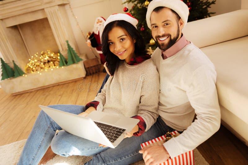 Hållande ögonen på film för älskvärda par på bärbara datorn på jul royaltyfria bilder