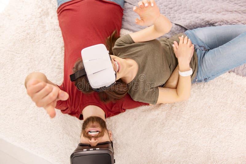 Hållande ögonen på film för charmiga gladlynta par i VR royaltyfri bild