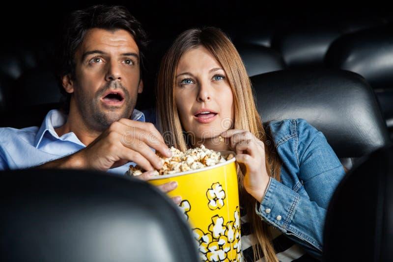 Hållande ögonen på film för chockade par i teater royaltyfria foton