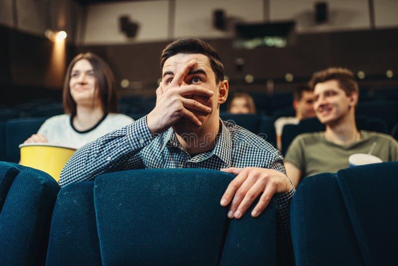 Hållande ögonen på film för förskräckt man i bio arkivbilder