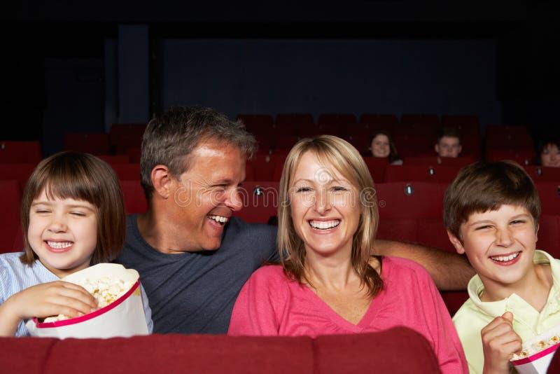 Hållande ögonen på film för familj i bio royaltyfria bilder