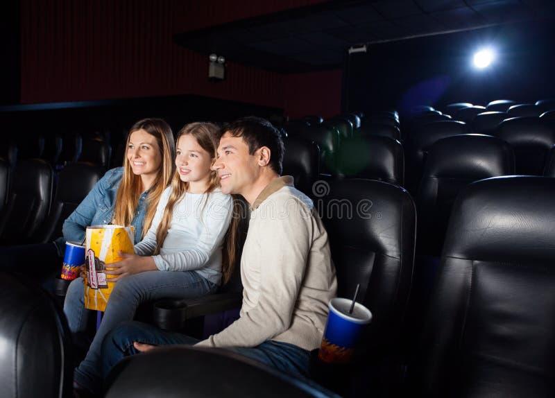 Hållande ögonen på film för familj i bioteater arkivfoto