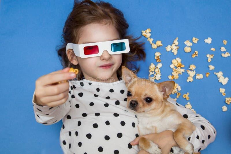 Hållande ögonen på film för flicka och för liten hund i exponeringsglas 3D med popcorn royaltyfri bild