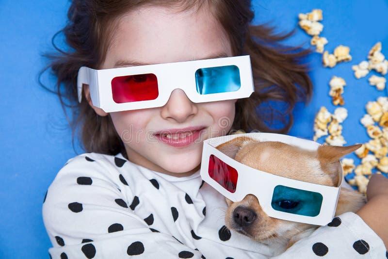 Hållande ögonen på film för flicka och för liten hund i exponeringsglas 3D med popcorn royaltyfri foto