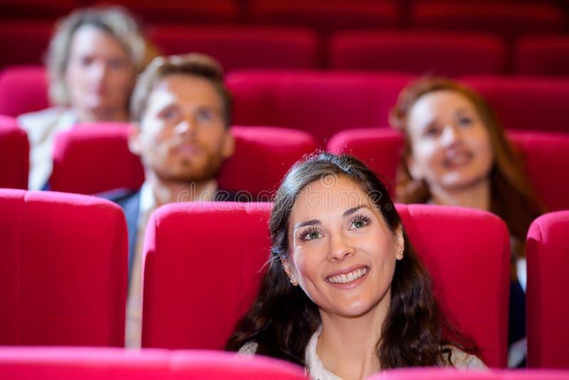 Hållande ögonen på film för folk på bion arkivbild