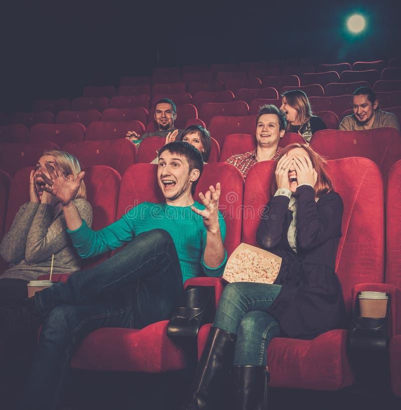 Hållande ögonen på film för folk i bio royaltyfria bilder