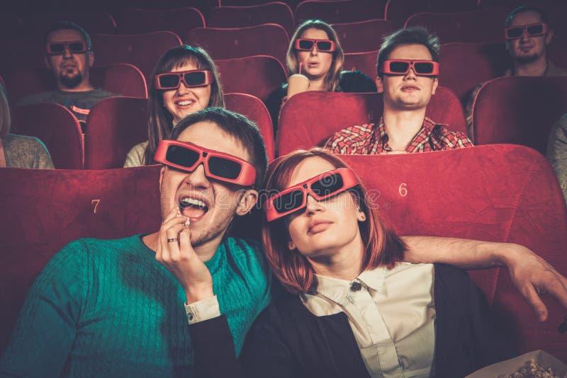 Hållande ögonen på film för folk i bio arkivbild
