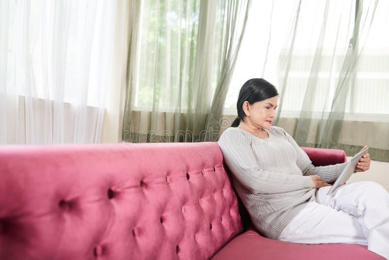 Hållande ögonen på film för kvinna på minnestavlan royaltyfri foto
